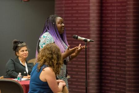 Participant speaking into microphone during Fall Symposium.